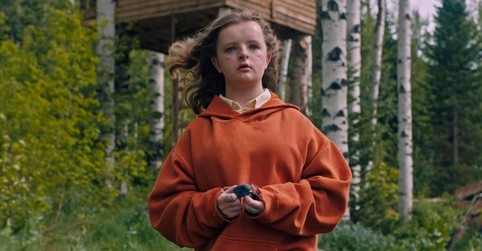 Charlie, from Hereditary, stands in a forest.