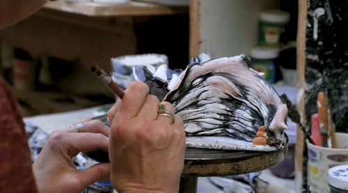 A hand painting pottery, in a screencap from the documentary 'Catching a Glimpse Of Beauty'